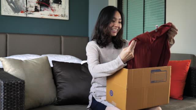 young woman opens cardboard box while sitting on a sofa at home - odzież filmów i materiałów b-roll
