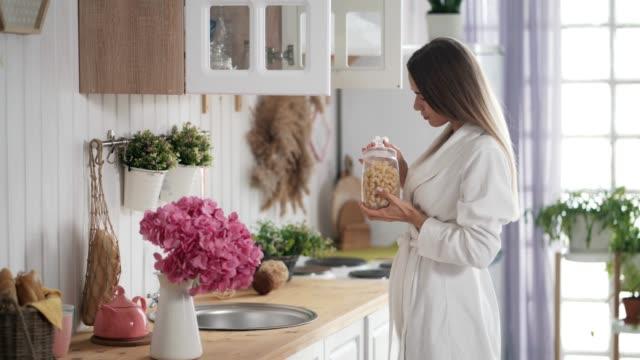 ung kvinna öppnar skåp i köket och tar ut en mat kanna - looking inside inside cabinet bildbanksvideor och videomaterial från bakom kulisserna