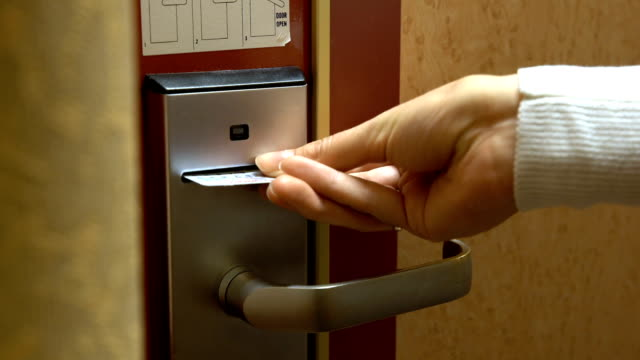 A young woman opens the door of his hotel room using an electronic key card. video
