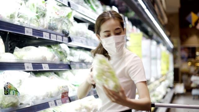 stockvideo's en b-roll-footage met jonge vrouw of meisje dat een gezichtsmasker draagt dat voedsel in supermarkt koopt - discountwinkel