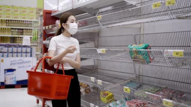 junge frau oder mädchen trägt eine gesichtsmaske kaufen lebensmittel im supermarkt - supermarkt einkäufe stock-videos und b-roll-filmmaterial