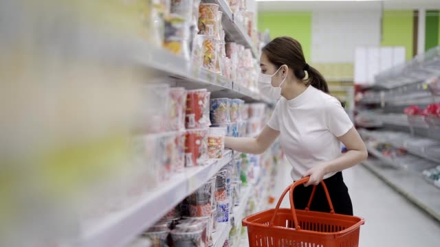 young woman or girl wearing a facial mask buying food in supermarket - дискаунтер стоковые видео и кадры b-roll