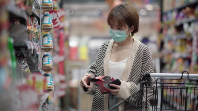stockvideo's en b-roll-footage met jonge vrouw of meisje dat een voedsel van de gezichtsmaskerhouder in supermarkt draagt - discountwinkel