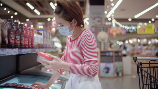Young woman or girl wearing a facial mask holder food in supermarket