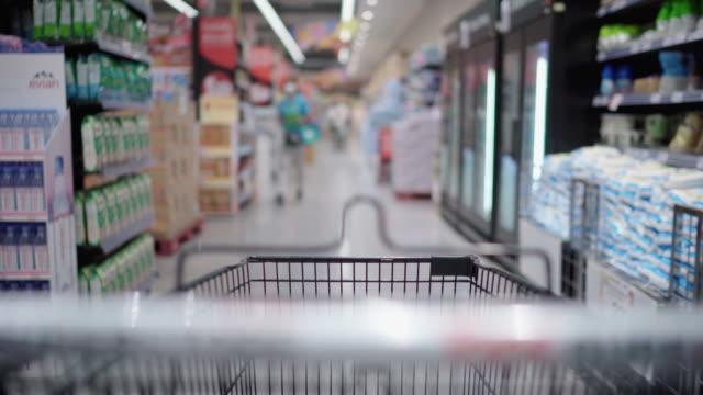 stockvideo's en b-roll-footage met jonge vrouw of meisje dat een voedsel van gezichtsmaskerhouders bij supermarkt draagt - discountwinkel