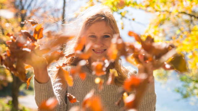 Young woman outdoors in nature on a windy autumn day