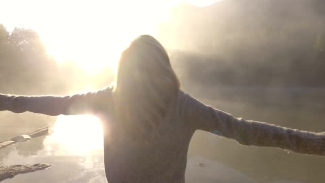 Young woman outstretches arms by the lake in the morning, wellbeing concept
