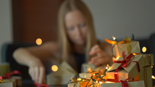 A young woman pack presents. She is tired of making so many presents prior to big holidays. Concept of tiredness from the Christmas and New year A young woman pack presents. She is tired of making so many presents prior to big holidays. Concept of tiredness from the Christmas and New year. resting stock videos & royalty-free footage