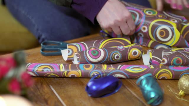 vídeos de stock e filmes b-roll de young woman packing christmas gift - coffee table