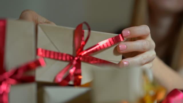 eine junge frau packt geschenke. geschenk verpackt in handwerkspapier mit einem roten und goldenen band für weihnachten oder neujahr. frau macht einen adventskalender für ihre kinder - advent stock-videos und b-roll-filmmaterial