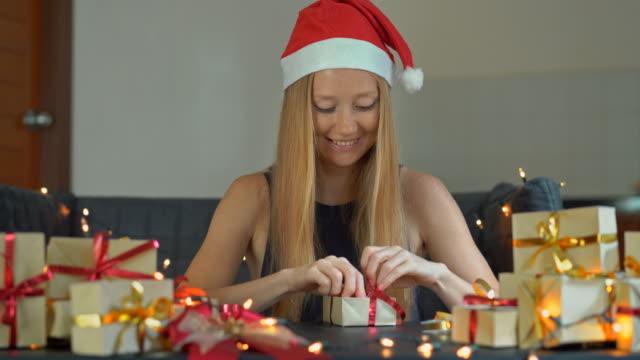 eine junge frau packt geschenke. geschenk verpackt in handwerkspapier mit einem roten und goldenen band für weihnachten oder neujahr. frau macht einen adventskalender für ihre kinder - adventskalender stock-videos und b-roll-filmmaterial