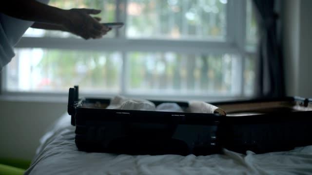 stockvideo's en b-roll-footage met jonge vrouw verpakken van koffer thuis. - ingepakt