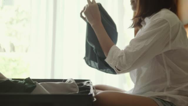 stockvideo's en b-roll-footage met jonge vrouw verpakking koffer - ingepakt