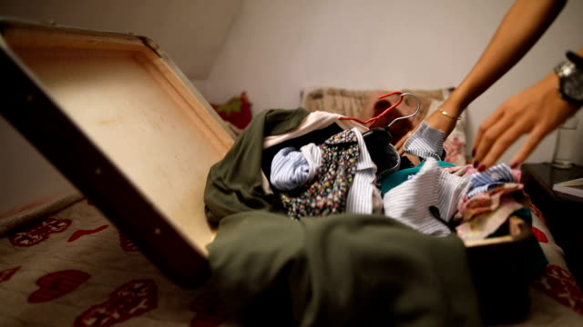 Young woman packs a suitcase for the trip in her room