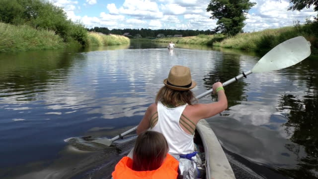 Young woman paddling canoe in river video
