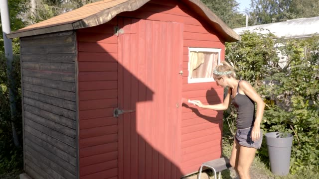 Young woman painting cabana in summer in the garden, people outdoor house activity concept