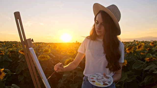 SLOW MOTION Young woman painting in the middle of sunflower field at sunset