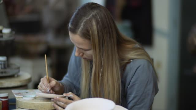vidéos et rushes de peinture de jeune femme sur la céramique faite à la main dans son atelier de poterie, concept de petite entreprise - pots de bureau