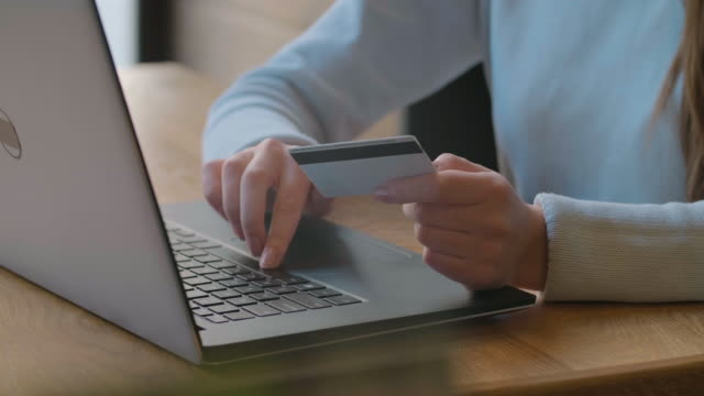 Young woman paying bill, shopping online, inserting credit card number. Attractive woman paying for online shopping using laptop and credit card. close up.