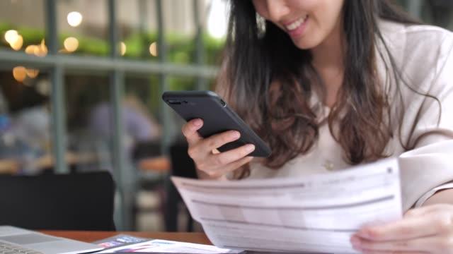 vidéos et rushes de jeune femme, payer des factures en ligne sur téléphone intelligent - main service