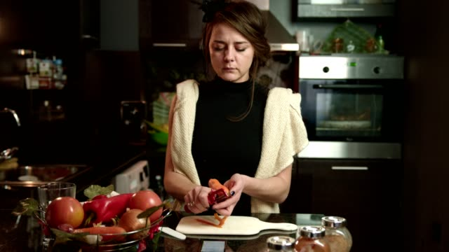 Young woman peeling a carrot on the kitchen counter video