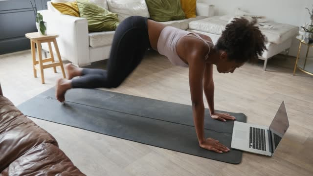 vídeos de stock e filmes b-roll de young woman performing mountain climbers in the lounge at home, online workout on the laptop - treino em casa