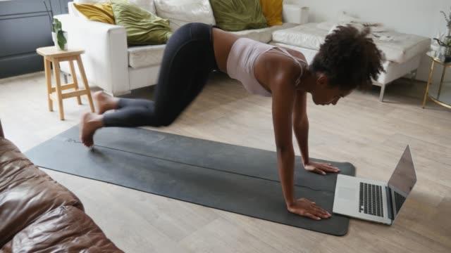 ung kvinna utför bergsklättrare i loungen hemma, online träning på den bärbara datorn - hemmaträning bildbanksvideor och videomaterial från bakom kulisserna