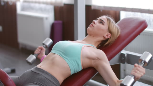 Young woman performs dumbbell flyes in gym video