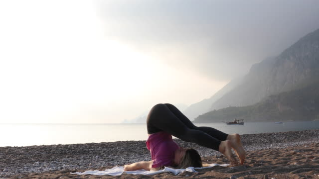 Young woman performs yoga moves on beach at sunrise