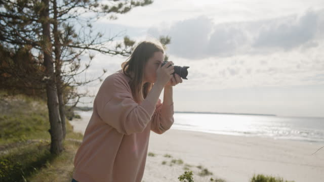 Young woman photographer takes pictures of the sea using digital camera
