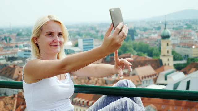 A young woman photographes herself against the cityscape of Graz in Austria. Euro-trip video