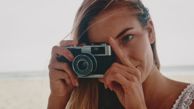 Young woman photographing through camera at beach