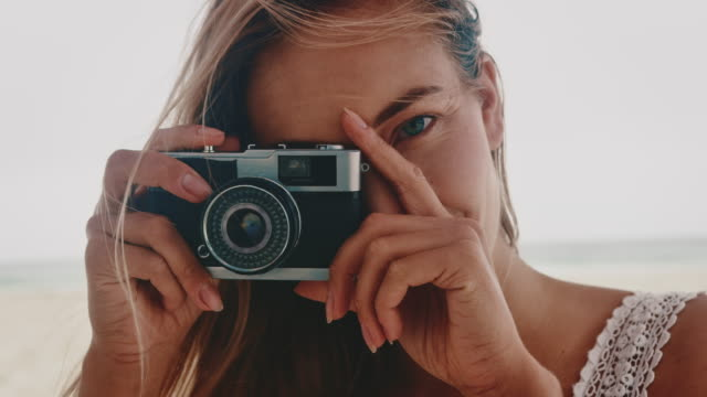 Young woman photographing through vintage camera
