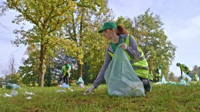 DS Young woman picking up litter scattered across a meadow with other volunteers