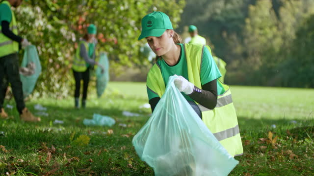 Young woman picking up rubbish off the ground in the meadow after an event