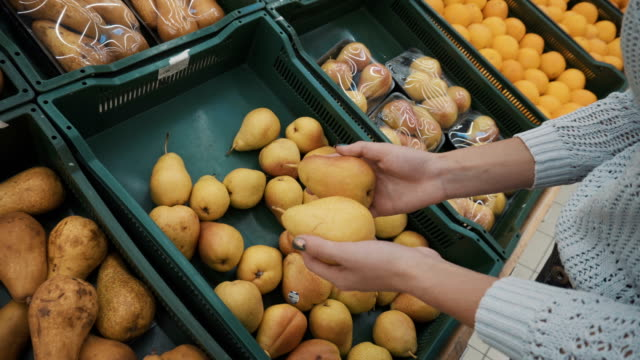 Young woman picks yellow pears at the market. Girl's hands close-up.