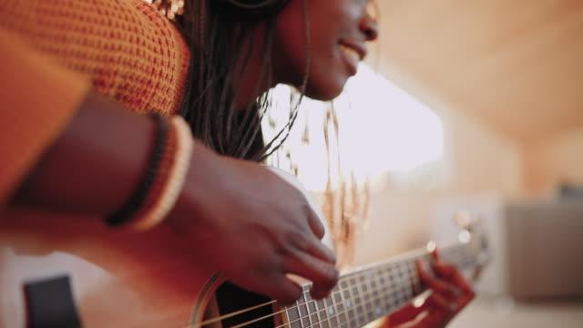 vídeos de stock e filmes b-roll de young woman playing acoustic guitar - compositor