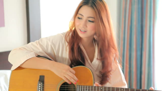 Young woman playing guitar video