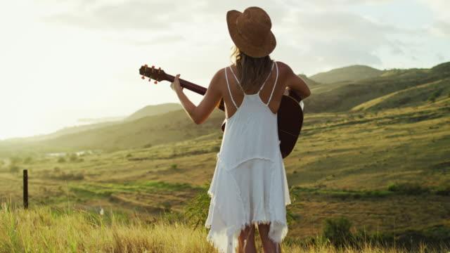 vídeos y material grabado en eventos de stock de joven mujer tocando la guitarra - músico