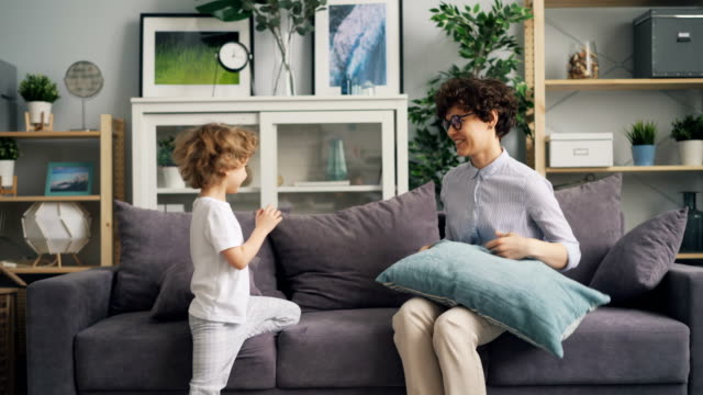 young woman playing hide-and-seek with son then having pillow fight and laughing - donna si nasconde video stock e b–roll