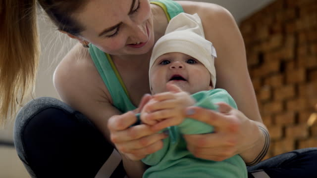 Young woman playing with baby sitting on floor indoors. Family, love and childhood concept video