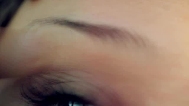 young woman plucking eyebrows with tweezers - depilacja filmów i materiałów b-roll