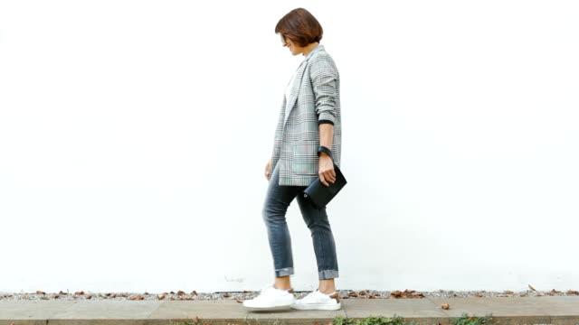 Young woman posing near white wall