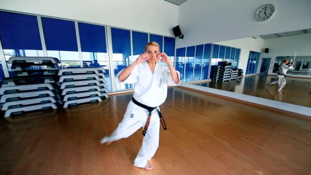 junge frau üben karate in der sporthalle - karate stock-videos und b-roll-filmmaterial