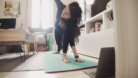 vidéos et rushes de jeune femme pratiquant le yoga à la maison - relaxation