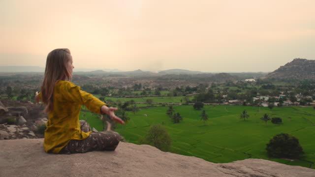 giovane donna che pratica yoga sulla scogliera di montagna all'alba - posizione corretta video stock e b–roll