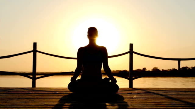 Young woman practicing yoga at sunrise video