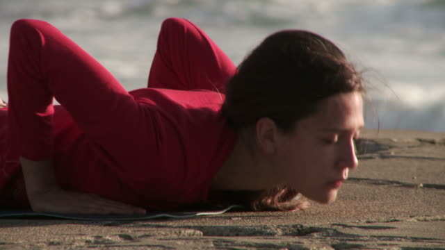 Young woman practicing yoga by the ocean video
