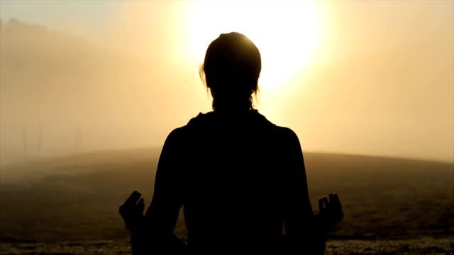 vidéos et rushes de jeune femme pratiquant l'yoga au lever du soleil - concentration