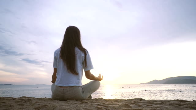 Young woman practicing yoga on the beach at sunrise.
